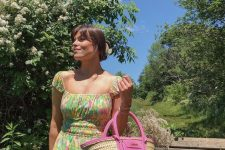 a bright floral summer mini dress with cap sleeves and a square neckline and a hot pink straw bag
