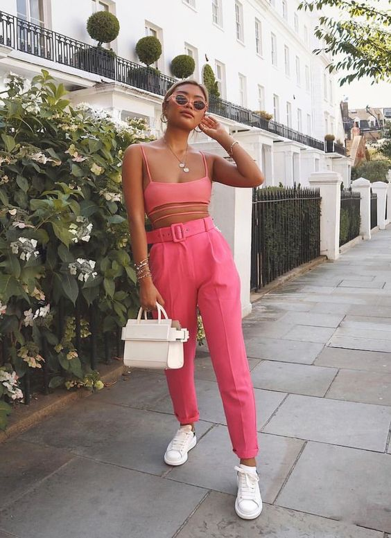 a bright look with a pink bra crop top, high waisted pants, white sneakers and a bag for a hot day