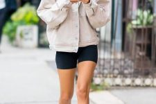 a bright neon tee, black biker shorts, a neutral oversized denim jacket and white sneakers