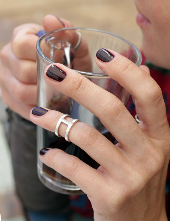 a burgundy manicure accented with a single silver midi statement ring looks wow