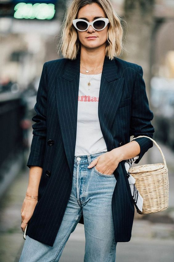 a casual outfit with a printed tee, blue jeans, a thin stripe blazer and a basket bag plus sunglasses