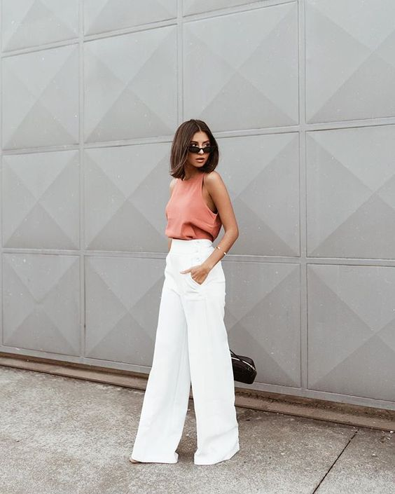 a coral halter neckline top, white palazzo pants and a black bag for a super bold look