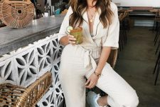 a creamy jumpsuit, white trainers, layered necklaces and a wooden bag for maximal comfort