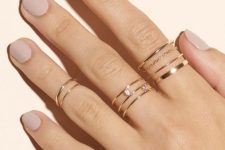 a delicate manicure is highlighted with gold rings with chains and rhinestones and gold midi rings
