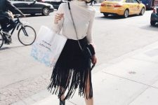 a fall look with a white turtleneck, a black fringe midi skirt, black flat boots and a hat