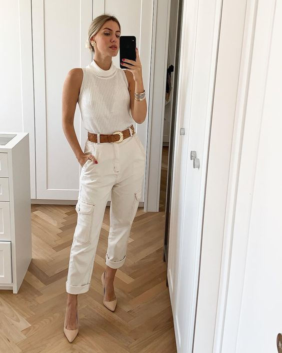 a glam outfit with a white halter top, white cargo pants, tan heels and a brown leather belt plus statement earrings