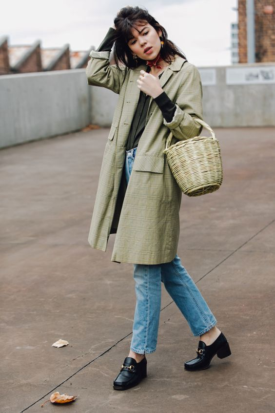 a green shirt, blue jeans, a green trench and black vintage-inspired shoes plus a basket