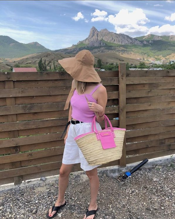 a hot pink crop top, white Bermuda shorts, black flipflops, a bucket hat and a hot pink raffia bag