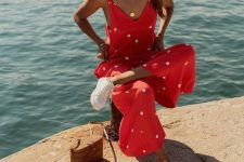a hot red polka dot jumpsuit with culottes, white sneakers and a small woven bag