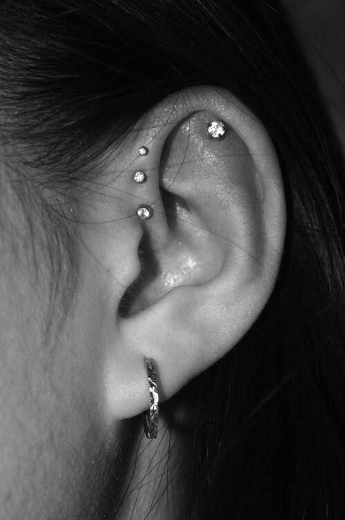 a lobe piercing, a flat piercing and stacked helix piercings accessorized with shiny studs and a hoop earring