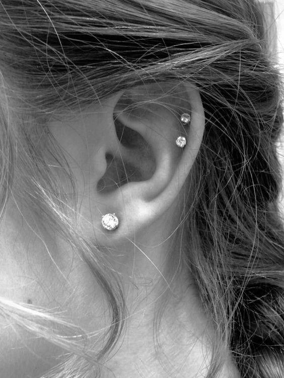 a lobe piercing and a double helix piercing accented with matching shiny studs look chic