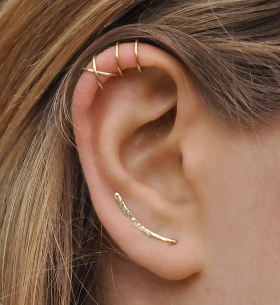 a lobe piercing with a long earring and stacked helix ones with hoop earrings for a minimalist look