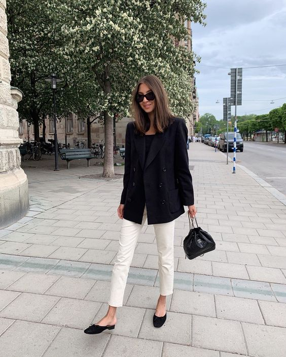 a monochromatic look for work with a black top, an oversized blazer and mules, white jeans and black top handle bag