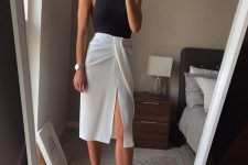 a monochromatic minimalist outfit with a black halter top and a layered wrap midi skirt, white minimalist heels