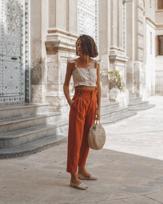 a neutral crop top with ruffle cap sleeves, rust-colored high waisted pants, white espadrilles and a woven bag