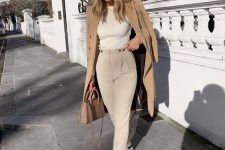 a neutral top, tan high waisted pants, white sneakers, a tan trench and a ten mini bag for work