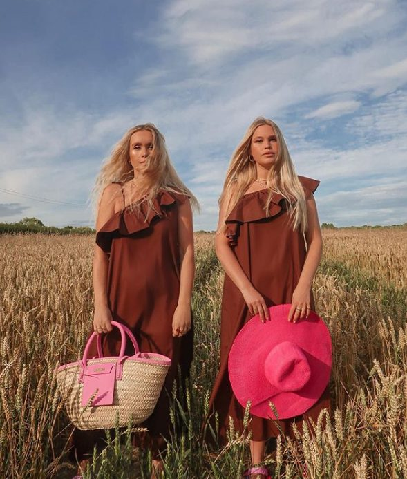 a one shoulder chocolate brown midi dress with a ruffle neckline, a hot pink raffia bag and the second girl with a hot pink hat