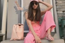 a pink strap top, pink paper bag pants, a pink cap, heels and a blush backpack for summer
