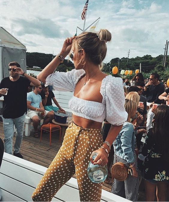 a playful outfit with a white lace puff sleeve crop top, mustard polka dot pants is bold