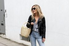a printed blouse, fit and flare jeans, nude strappy sandals, a black leather jacket and a basket bag