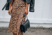 a printed tee, a leopard print midi skirt, white sneakers, a black leather jacket and a black bag