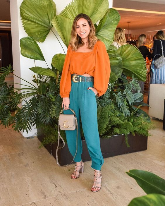 a special occasion look with an orange crop top with long puff sleeves, green pants, silver shoes and a shiny bag