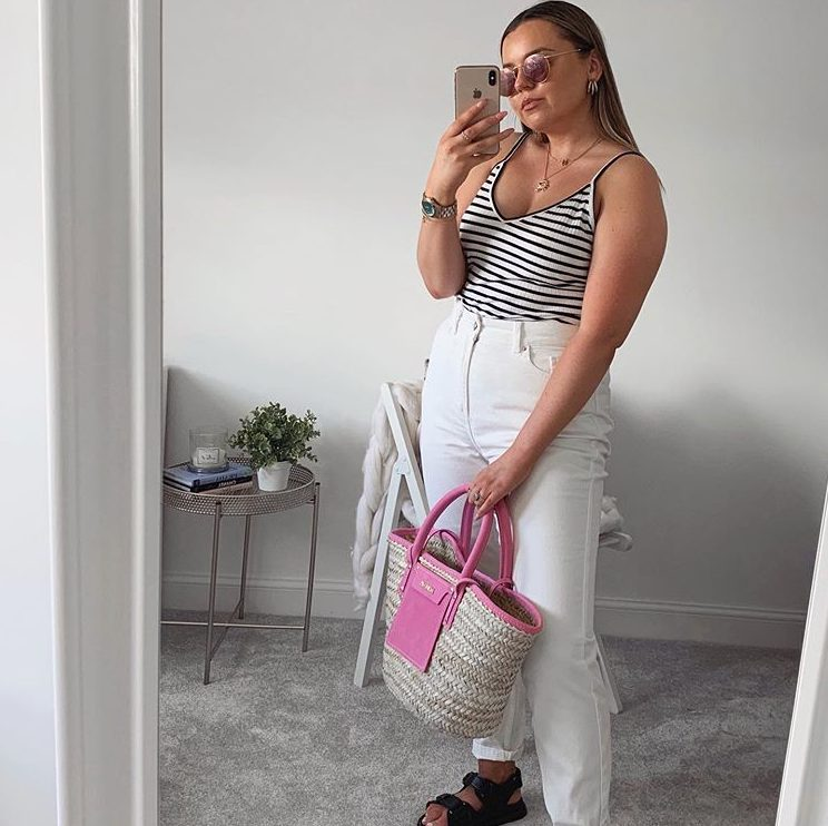 a striped black and white top, white jeans, black daddy sandals and a hot pink raffia bag plus pink sunglasses