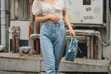 a stylish outfit with blue jeans, a floral crop top with puff sleeves, a powder blue bag and white sneakers