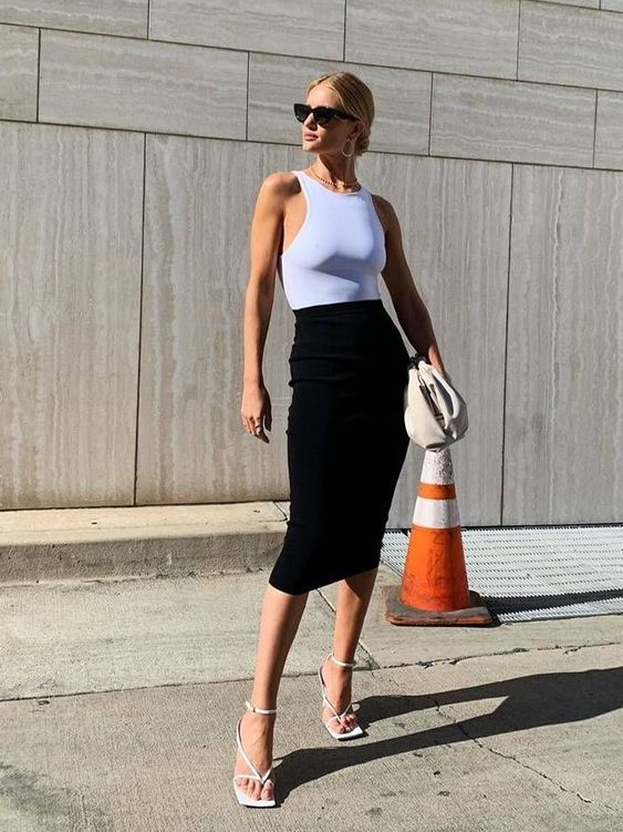 a stylish summer work look with a white halter top, black midi skirt, white square toe heels and a white clutch