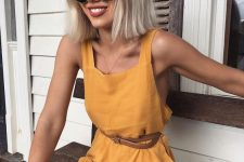 a sunny yellow linen romper with thick straps and a thin leather belt is chic and sexy