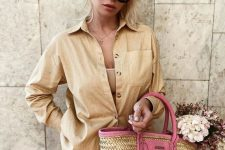 a tan linen suit with an oversized shirt and wide shorts, a nude top and a hot pink raffia bag for an accent