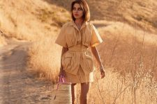 a tan skirt costume with a catchy layered and ruched top with short sleeves, white heeled sandals and a large hot pink straw bag