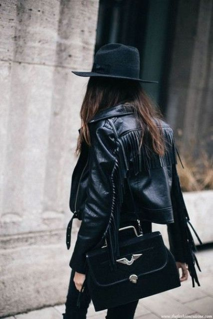 a total black look with a cropped leather fringe jacket, a hat and a statement chic bag