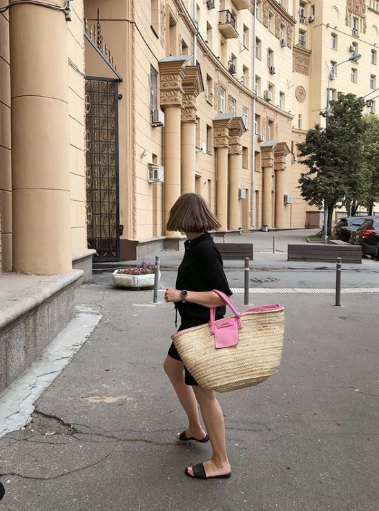 a total black look with a short sleeved shirt and Bermuda shorts, black slippers and a hot pink raffia bag
