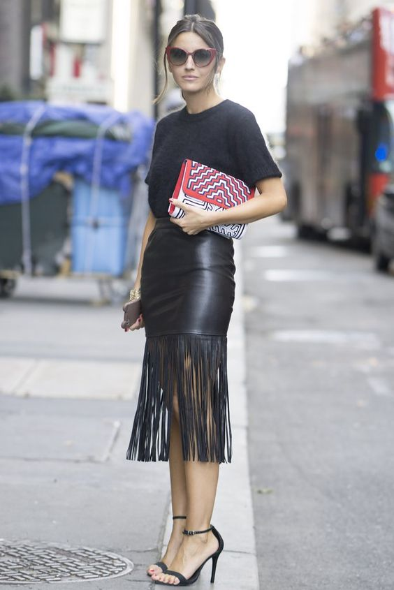 a total black look with a tee, a leather fringe midi skirt, heels and red frame glasses