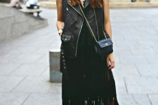 a total black outfit with a top, a fringe midi skirt, a leather waistcoat, shoes and a crossbody
