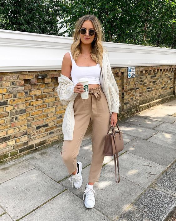 a whiet crop top, tan paper bag pants, white sneakers, a white knit cardgian and a chocolate brown bag