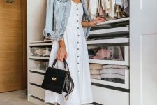 a white A-line midi dress, a denim jacket, white sneakers and a black top handle bag