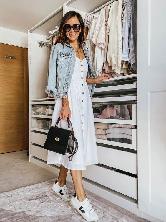 a white A-line midi dress, a denim jacket, white sneakers and a black top handle bag