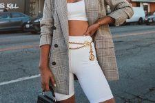 a white crop top and biker shorts, an oversized plaid blazer, a gold chain belt and a black mini bag