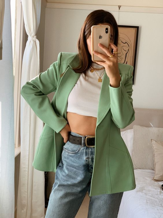 a white crop top, blue high waisted jeans, an apple green blazer and layered necklaces