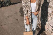 a white crop top, blue jeans, a snake print blazer, tan heels and a tan mini bag