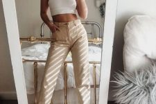 a white halter crop top, tan high waisted jeans, white trainers for a 90s inspired look