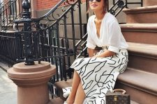 a white shirt, a printed A-line midi skirt, white sneakers and a stylish mini top handle bag