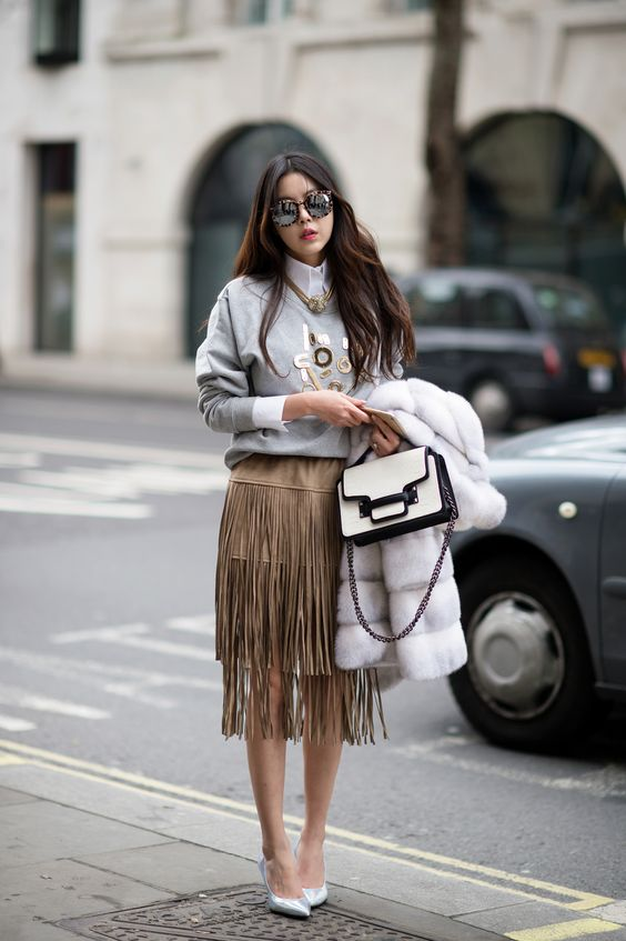 a white shirt, an embellished sweatshirt over it, a tan fringe midi skirt, silver shoes and a two-tone bag