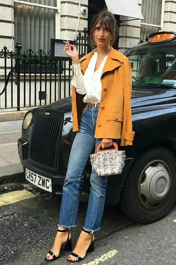 a white shirt, blue jeans, a yellow vintage jacket, black heels and a small and cute top handle bag