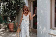 a white silk spaghetti strap top, a polka dot midi skirt, white lace up heels and a brown bag