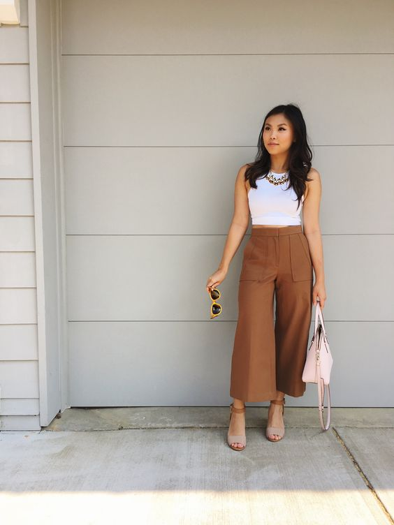 a white sleeveless top, brown culottes with pockets, chain necklaces, two tone shoes and a pink bag