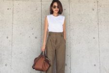 a white sleeveless top, green high waisted pants, black shoes and a brown bag for a minimal look