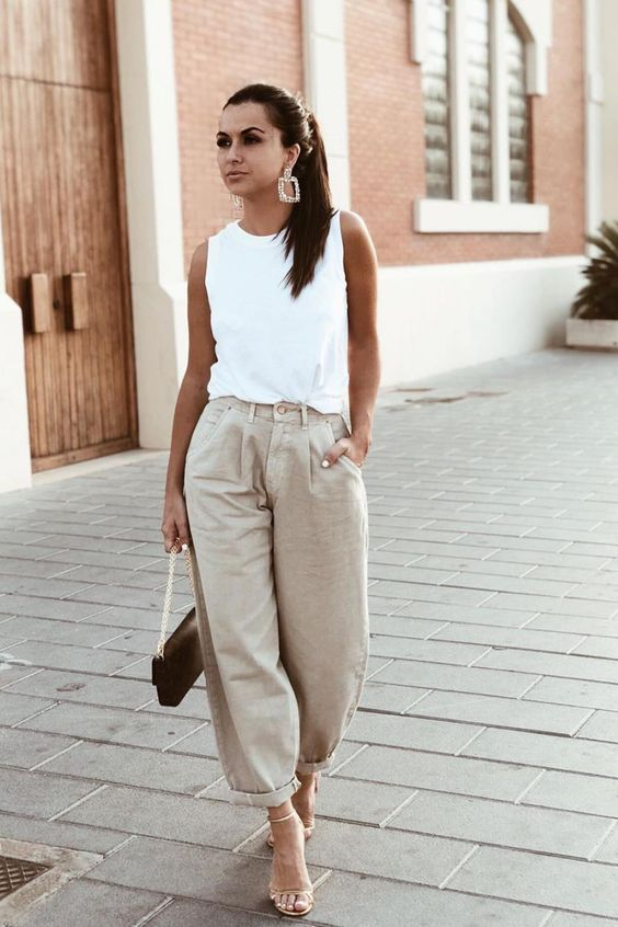 a white sleeveless top, neutral slouchy jeans, tan heels and a black bag for an edgy look